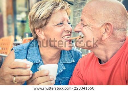 Happy playful senior couple in love tenderly enjoying a cup of coffee - Joyful elderly active lifestyle - Man having fun and smiling with her wife in a bar cafe restaurant during vacation - stock photo