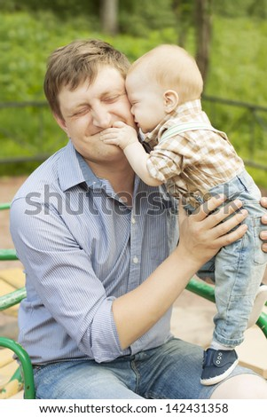 Happy playful son hugging and kissing his laughing father - stock photo