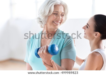 Happy pleasant woman holding a blue dumbbell
