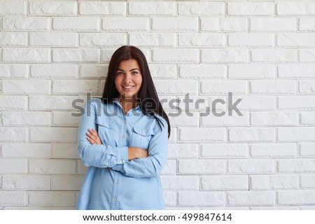 Happy pleased woman in casual blue-light outfit smiling with arms crossed against a white brick background