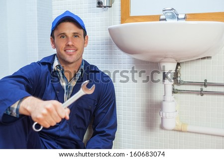 Happy plumber holding wrench sitting next to sink in public bathroom - stock photo