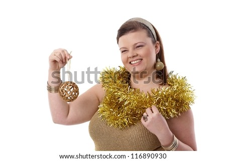 Happy plump woman holding christmas ornaments in hand, smiling. - stock photo