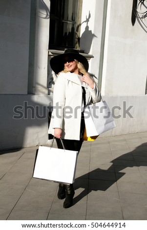 Happy plus size woman holding shopping bags on the street