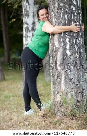 Happy plus sized woman stretching and hugging a tree