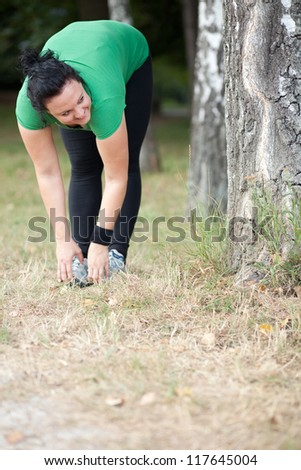 Happy plus sized woman stretching in the woods/ forrest - stock photo