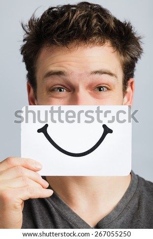Happy Portrait of a Man Holding a Smiling Mood Board - stock photo
