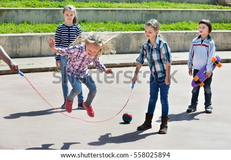 Happy positive children playing skipping rope jumping game and laughing outdoors