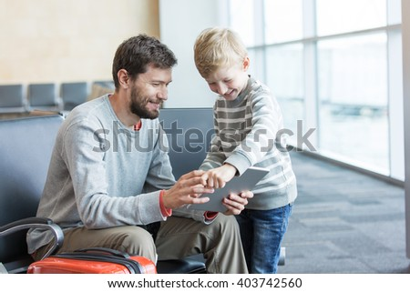 happy positive family of two, father with a beard and little son, at the airport waiting for departure and playing at tablet, travel and technology concept
