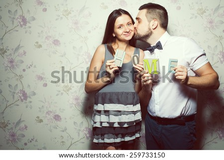 Happy pregnancy concept. Portrait of funny hipsters in stylish clothing kissing and posing together with letters making HOME word. Vintage style. Copy-space. Studio shot - stock photo