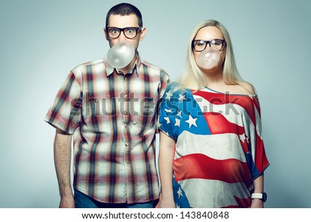 Happy pregnancy concept: portrait of two funny hipsters (husband and wife) in trendy glasses and clothes playing with their bubble gums. Copy-space. Studio shot - stock photo