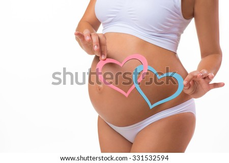 Happy pregnancy. Smiling pregnant woman holding a plate with two hearts. Mother Love. Twins, girl, boy. - stock photo