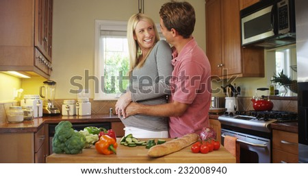 Happy pregnant couple in the kitchen - stock photo