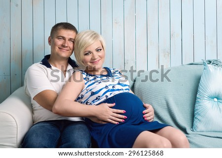 Happy pregnant couple sitting on the sofa at home