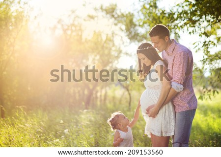 Happy pregnant couple with daughter touching belly in summer nature - stock photo