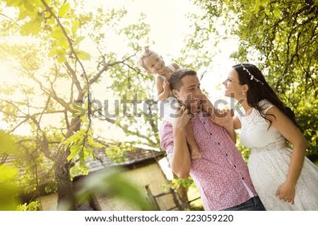 Happy pregnant family having fun in garden near the old farmhouse - stock photo