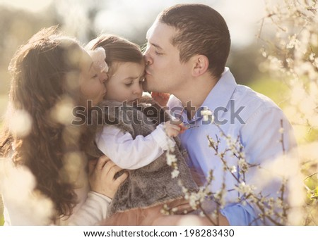 Happy pregnant family having fun in spring nature - stock photo