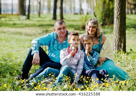 Happy pregnant family with two sons, dressed in a turquoise clothes sitting on grass with flowers at park