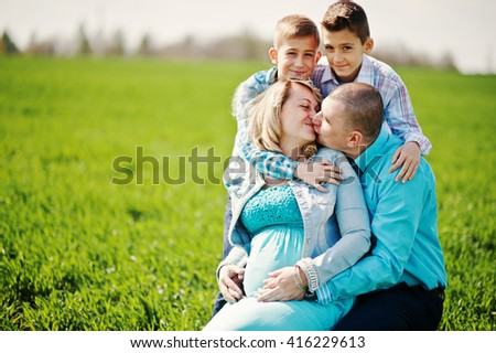 Happy pregnant family with two sons, dressed in a turquoise clothes, spending time together at green grass at field