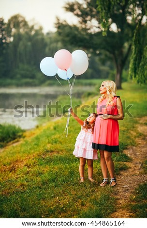 happy pregnant mother is walking with her little daughter in the park, happy family photo. Mother hold baloons. Family walk neaar lake. Beauty blond mother.