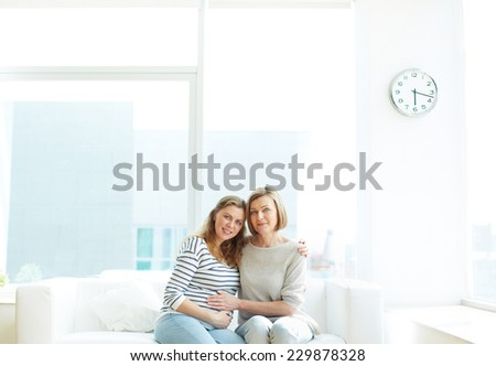 Happy pregnant woman and her mother sitting and embracing - stock photo