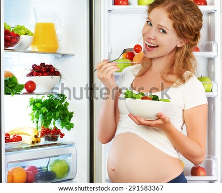 Happy pregnant woman eating salad near refrigerator at home