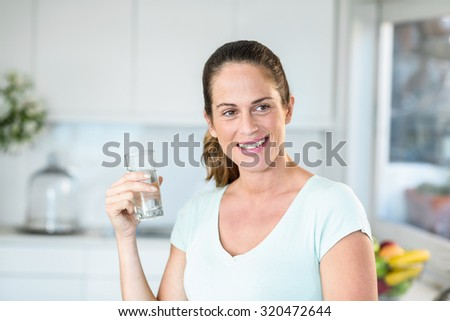Happy pregnant woman holding water glass while standing in kitchen