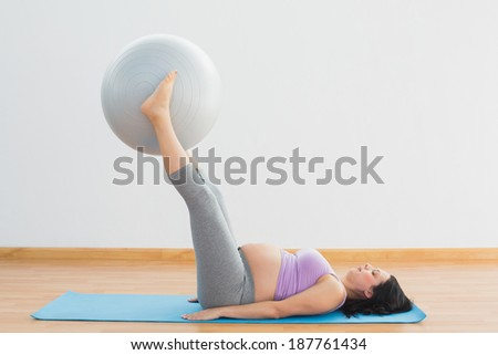 Happy pregnant woman lifting exercise ball with legs in a fitness studio - stock photo