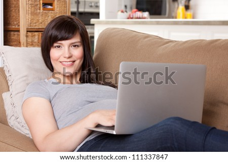 Happy pregnant woman looking at camera using laptop computer