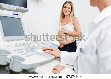 Happy pregnant woman looking at obstetrician using ultrasound machine in clinic - stock photo