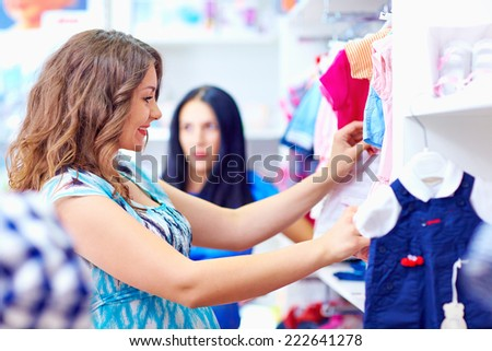 happy pregnant woman shopping in baby store - stock photo