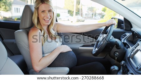 Happy pregnant woman sitting in car smiling - stock photo