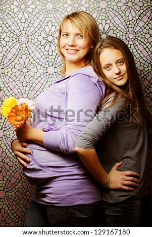 happy pregnant woman with daughter - stock photo
