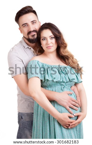 Happy pregnant woman with her husband isolated over white background. Studio shooting. Pregnancy. Motherhood and pregnancy