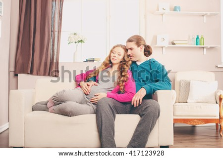Happy pregnant woman with her husband on a sofa in the room - stock photo