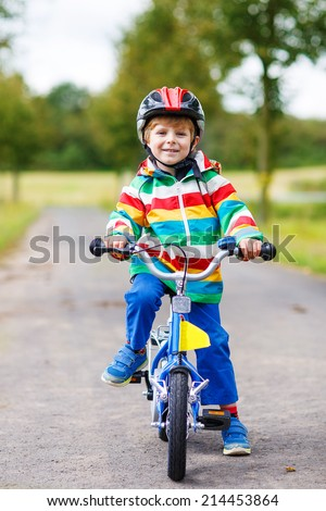 Happy preschool boy in red safety helmet and colorful raincoat riding his first bike on summer day.