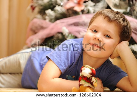 Happy preschool boy portrait outside with decorated Christmas trees - stock photo