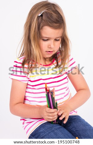 Happy preschool girl in striped blouse holding variety of colored pencils