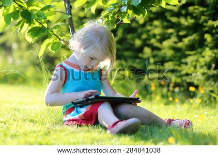 Happy preschooler child playing with tablet pc sitting in the garden on the grass. Cute little girl relaxing outdoors in the park enjoying sunny summer day. Young generation leisure. - stock photo