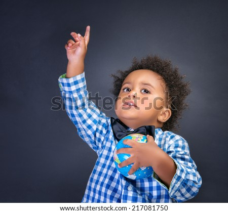 Happy preschooler discovering world, african boy with raised up hand understand something and holding globe in another,  geography lesson, back to school concept - stock photo