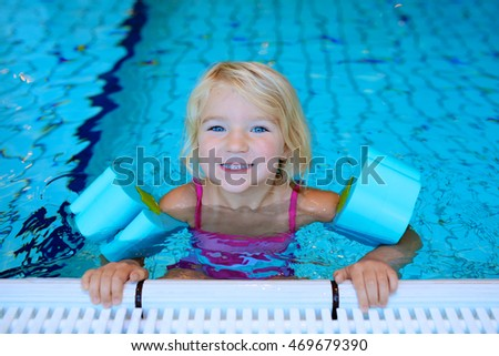 Happy preschooler girl learning to swim in community swimming pool. Little swimmer enjoying group lesson at sport school.