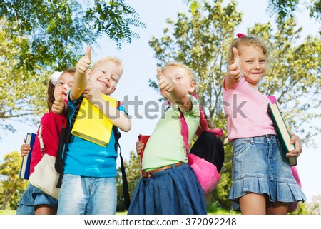 Happy preschoolers showing thumbs up - stock photo