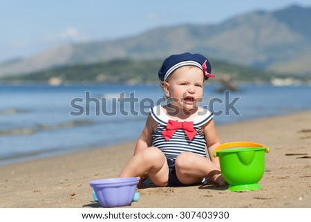 Happy pretty baby girl in swimsuit playing with sand on beach