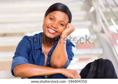 happy pretty black college girl looking at the camera - stock photo