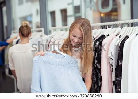 Happy Pretty Blond Lady Shopping for an Affordable Nice Trendy Dress Inside a Clothing Store. - stock photo