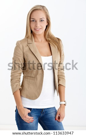 Happy pretty blonde girl in trendy jeans and jacket, smiling at camera.