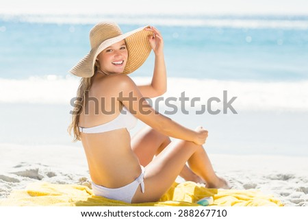 Happy pretty blonde looking at camera at the beach - stock photo