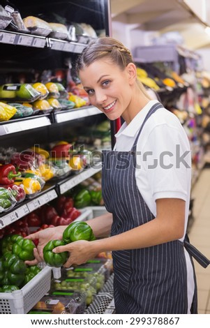 Happy pretty blonde putting green pepper on shelf in supermarket
