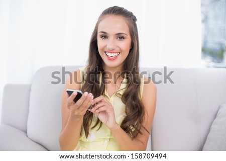 Happy pretty brunette holding smartphone in bright living room