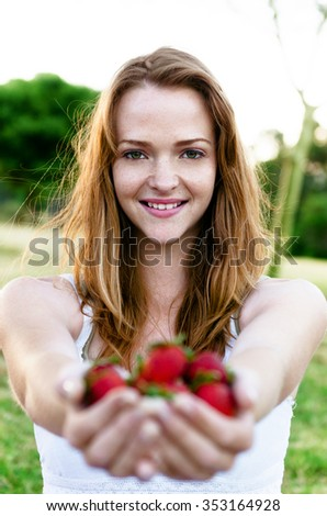Happy pretty carefree summer girl holding strawberries in her hands, at a green park field - stock photo