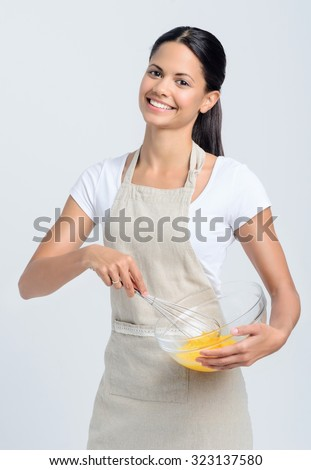 Happy pretty chef beating eggs in a glass bowl - stock photo